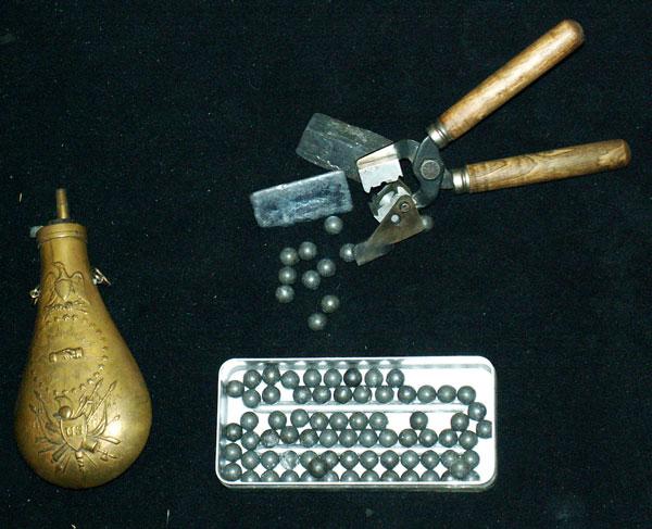 lingots de plomb, le moule, les balles, et la poire à poudre.